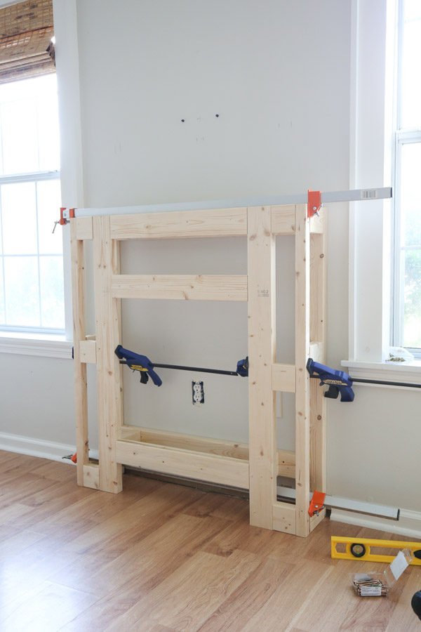 attaching front frame of DIY fireplace surround to back frame with clamps and screws