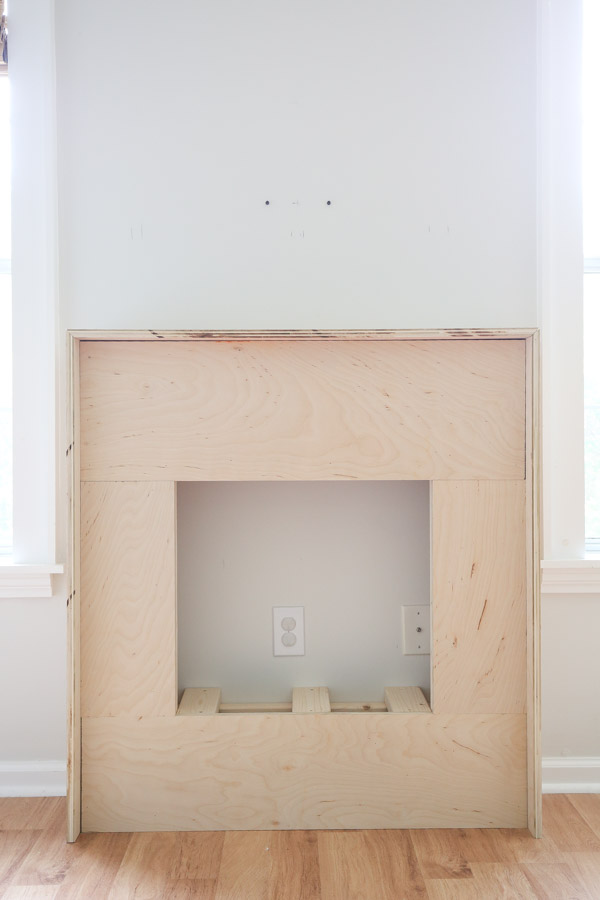 first layer of plywood installed on fireplace frame